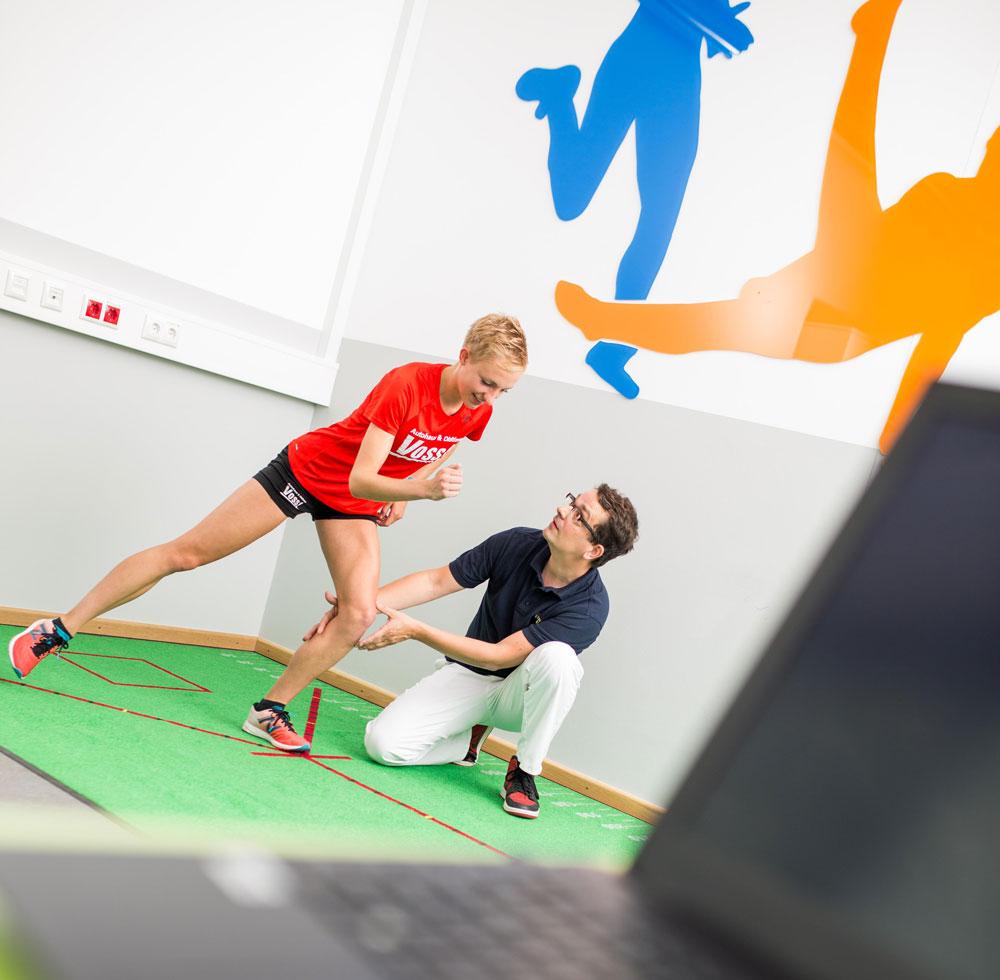 Frau beim Bewegungstraining mit Physiotherapeuten in Sportphysiotherapie in Münster